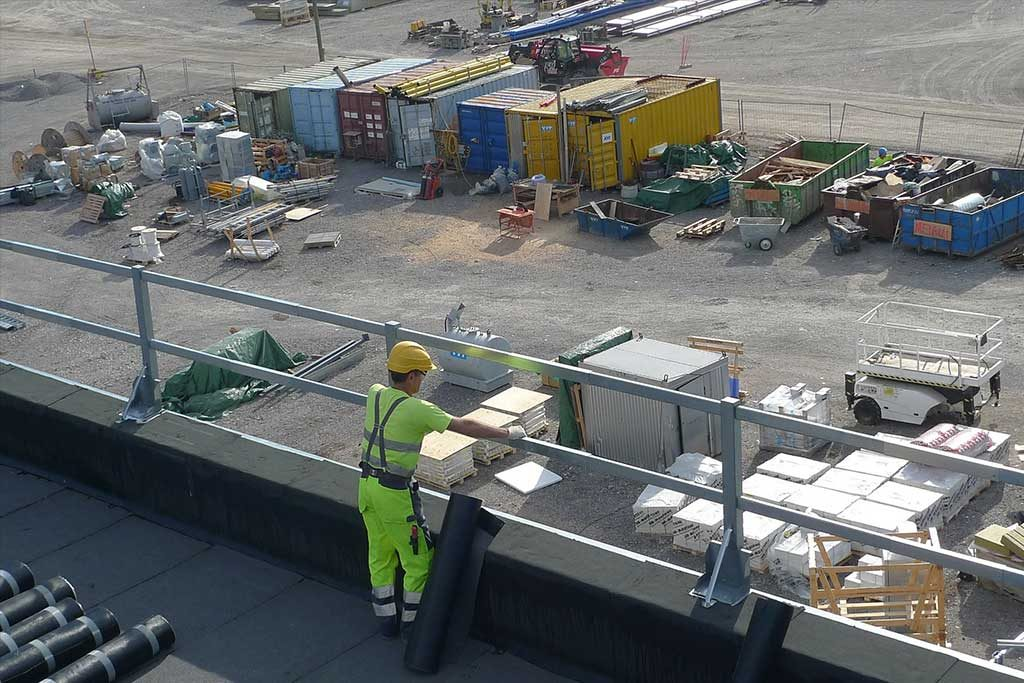 Commercial roofing contractor on flat roof with materials
