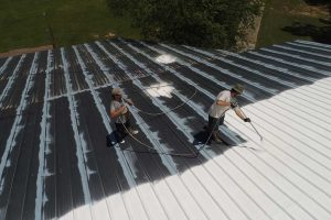 Roofing contractors coating a commercial roof